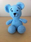 Billede af en lille hæklet blå bamse der sidder ned.