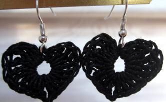 Et par øreringe der er hæklet sorte hjerter.
